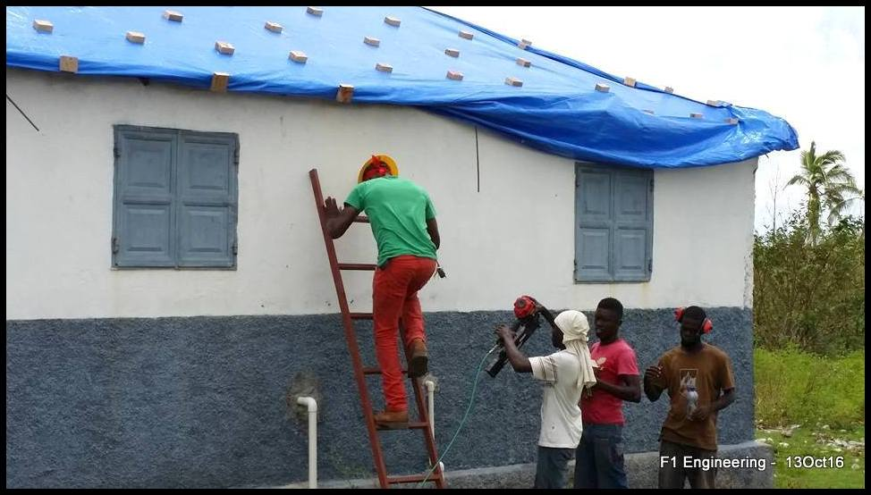 Securing the tarp on the clinic roof.